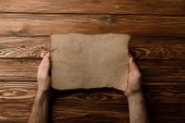 Fotografia top view of man holding aged paper sheet in hands