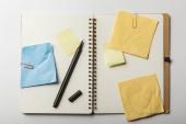 pohled shora otevřený notebook s modrými a žlutými rychlé poznámky s sponky na bílém pozadí