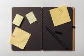 pohled shora otevřený notebook s černými listy a žluté rychlých poznámek s sponky na bílém pozadí