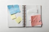 pohled shora otevřený notebook s hranatými papírů a poznámek sticky notes na bílém pozadí