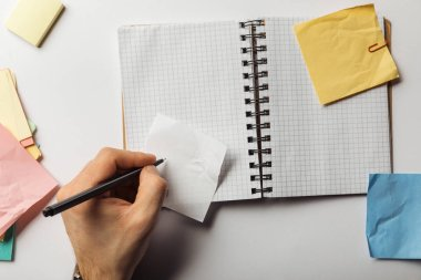 Cropped view of man writing on sticky note near opened notebook stock vector