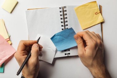 Cropped view of man writing on sticky note and holding crumpled blue paper near opened notebook stock vector