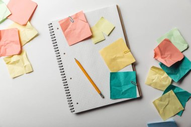 top view of notebook with blank squared page near crumpled colorful sticky notes on white background