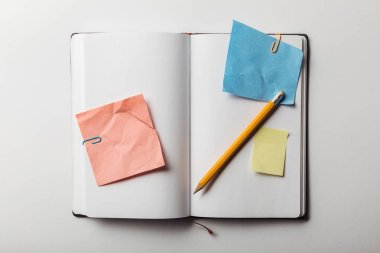 top view of opened notebook with sticky notes and paper clips near pencil on white background