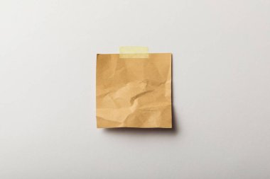 brown blank paper with sticky tape on white background