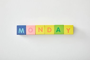 top view of monday lettering made of multicolored cubes on white background