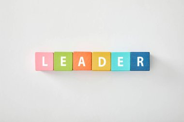 top view of leader lettering made of multicolored blocks on grey background
