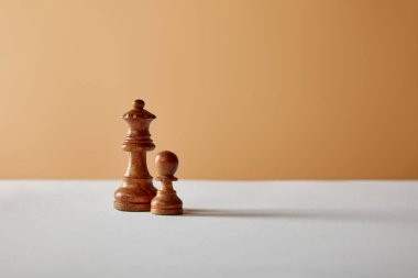 wooden queen and pawn pieces on white table and beige background
