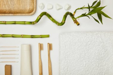 top view of towel, ear sticks, toothpaste in tube, cosmetic cream, toothbrushes, stones and bamboo stem on white background
