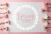 a rózsaszín háttér gyönyörű rózsaszín és fehér szegfű és a kártya-val kerek keret tavaszi betűjelzést felülnézet