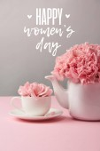 Fotografie pink carnation flowers in cup and teapot on grey background with happy womens day lettering