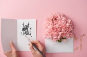 cropped view of woman holding greeting card with trust your soul lettering and pen near carnation flowers in envelope on pink background