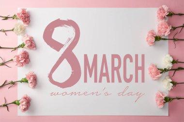 """Картина, постер, плакат, фотообои """"верхний вид красивых розовых и белых гвоздик цветы и 8 марта поздравительная открытка на розовом фоне """", артикул 246318660"""