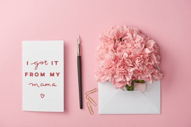 Top view of mothers day greeting card and envelope with carnations on pink background stock vector