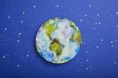 Fotografie Draufsicht auf Planetenbild auf violettem Hintergrund mit Sternen, Earth Day-Konzept