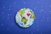 top view of planet picture with heart symbol on violet background with stars, earth day concept