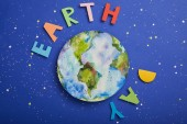 Fotografie top view of colorful paper letters and planet picture on violet background with stars, earth day concept