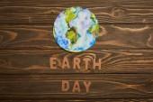 pohled shora papírové dopisy a planeta obrázek na hnědé dřevěné pozadí, koncept den země