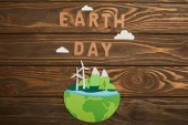 top view of paper cut planet with renewable energy sources and paper letters on wooden background, earth day concept
