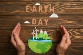 partial view of woman holding paper cut planet with renewable energy sources and letters on wooden background, earth day concept