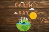 top view of paper cut planet with renewable energy sources and letters on wooden background, earth day concept