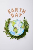 top view of fresh green fern leaves with paper letters and planet picture isolated on grey background, earth day concept