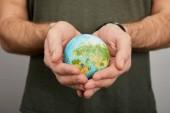 uomo che tiene il modello del pianeta su sfondo grigio, concetto di giorno di terra