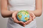 žena držící model planety na šedém pozadí, koncept den země