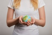 Fotografie woman holding planet model on grey background, earth day concept