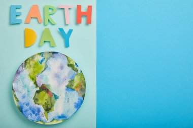 Top view of colorful paper letters and planet picture on green and blue background, earth day concept stock vector