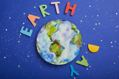 top view of colorful paper letters and planet picture on violet background with stars, earth day concept