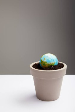 planet model placed in flowerpot with soil on table surface, earth day concept