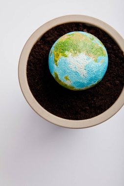 top view of planet model placed on flowerpot with soil, earth day concept