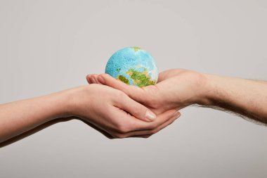 man and woman holding planet model on grey background, earth day concept