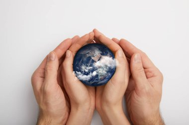top view of man and woman holding planet model on grey background, earth day concept
