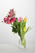 Photo fresh pink roses and yellow tulips in glass jar isolated on white