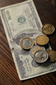 Fotografie selective focus of dollar banknote and coins on wooden table