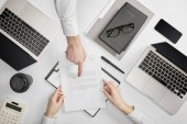 Fotografie top view of businessman pointing to contract to clerk