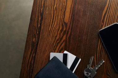 top view of credit cards, smartphone, keys and wallet on wooden surface