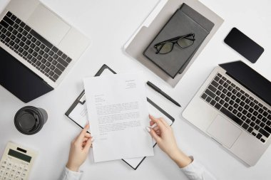 partial view of office worker holding contract at workplace
