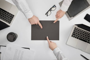 Top view of businesspeople pointing to blank grey paper at workplace stock vector