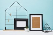 black frames near green plant in pot and metallic holders on table
