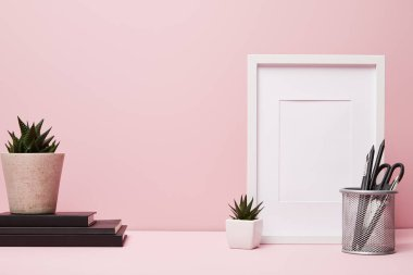 blank frame near green plant, metallic holder with stationery and books