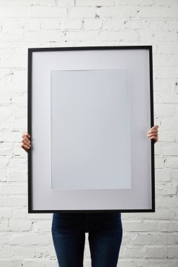 woman covering face while holding blank black frame in hands