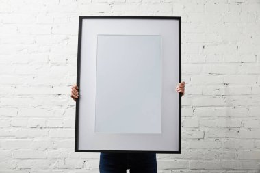 Woman covering face while holding blank black frame stock vector