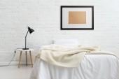 moderní ložnice s postelí a černý rám na bílé zdi