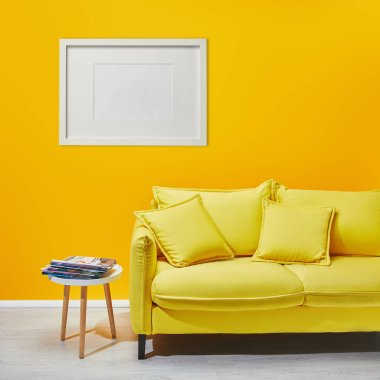 Coffee table standing near modern yellow sofa near white frame hanging on wall stock vector