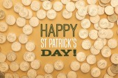 top view of golden shiny coins near happy st patricks day lettering on orange background