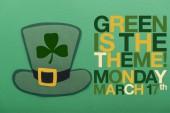 green irish paper hat near lettering on green background