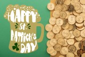 top view of golden coins near happy st patricks day lettering on green background